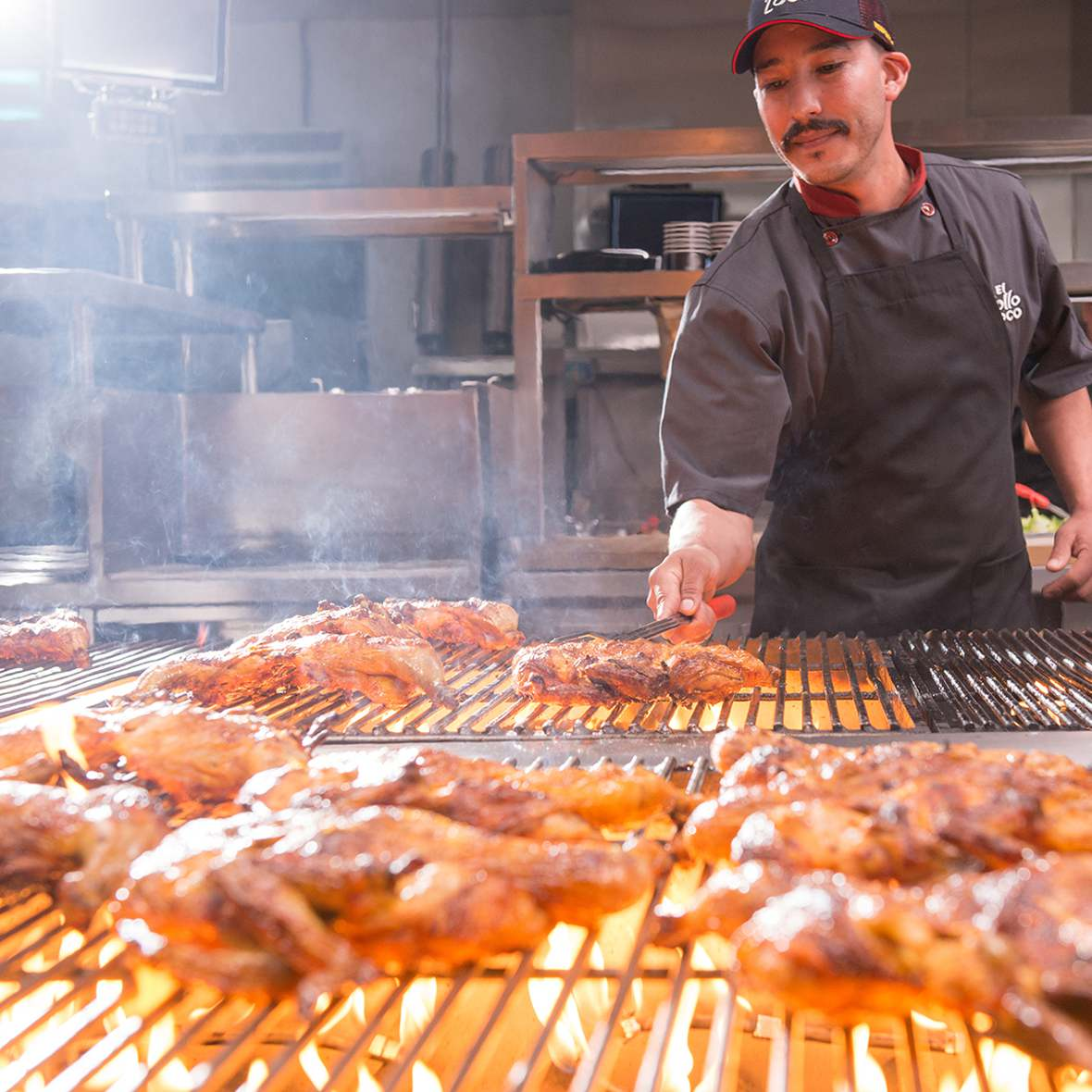 Grill master cooks citrus-marinated chicken over open flame